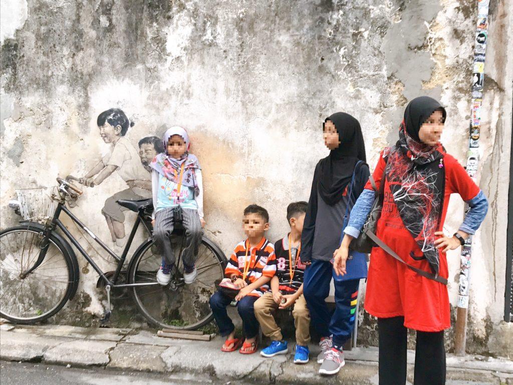 ペナン島のウォールアート「Kids on Bicycle」で写真を撮るムスリム