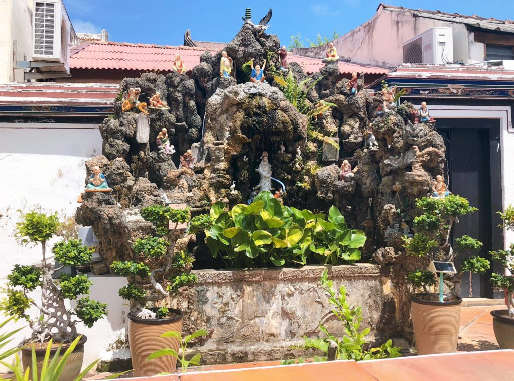 チェン・フーン・テン・テンプルの神様の彫刻が置かれた岩
